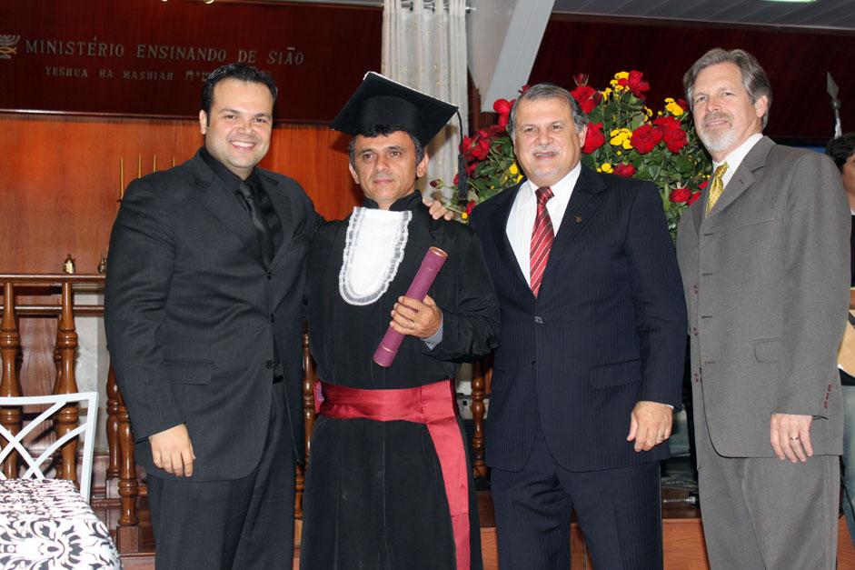 O Formando José Humberto Martins, do Ceará, recebe seu diploma das mãos dos diretores do Curso